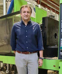 Carlos Godoy vicino un macchinario di stampaggio pinne